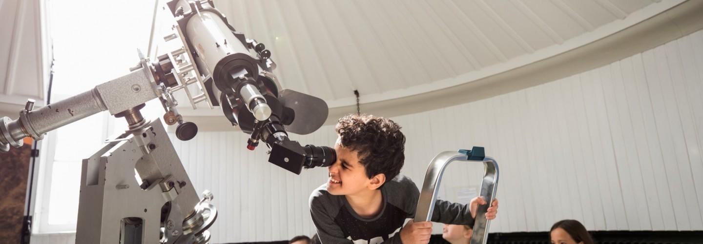 Een jongetje kijkt door de zonnetelescoop van Sonnenborgh