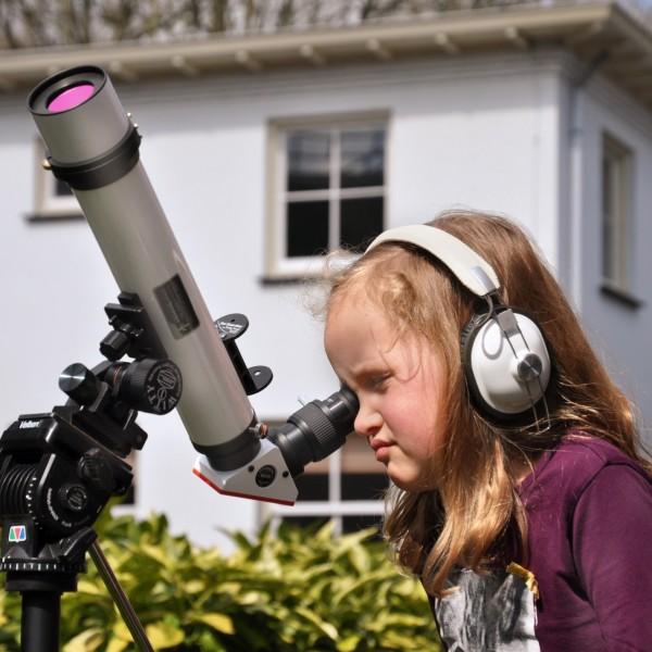 Een meisje kijkt door een telescoop naar de zon in de tuin van Sonnenborgh